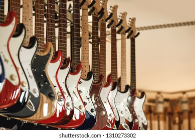 Buying electric guitar. Stand with various colorful electric guitars in music shop. Musical instrument