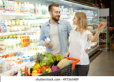 Buying food. Shot of an attractive young woman pointing away at the supermarket showing something to her handsome boyfriend while choosing food together