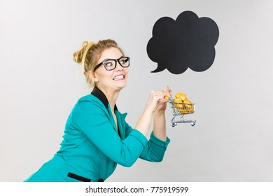 Buying gluten food products concept. Bussines woman holding shopping cart trolley with sweet bun, black thinking or speech bubble next to her.