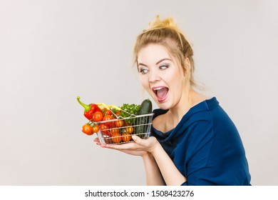 Buying good food, vegetarian products. Positive woman holding shopping basket with green red vegetables inside, recommending healthy high fibre diet, lifestyle modification, on grey