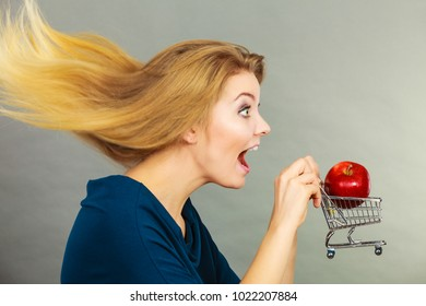 Buying healthy food, vegetarian, gluten free, vegan products. Happy woman with windblown hair holding shopping cart with apple inside
