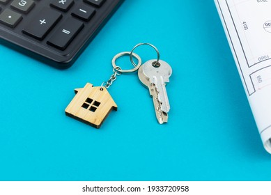 Buying a house or mortgage concept. Keys with calculator and plan on blue background. Housing and Real Estate concept.