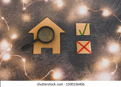 buying or moving house concept, miniature cardboard house with green tick and cross options to choose the best property