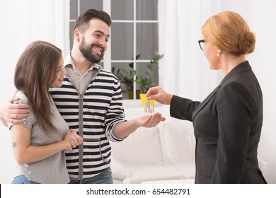 Buying new apartment. Young family just purchased new apartment. Happy man and woman receiving keys for new home.