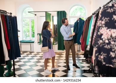 Buying a new blazer. Attractive nice-looking handsome mature man in stylish clothing choosing a new blazer along with his beautiful lovely charming wife