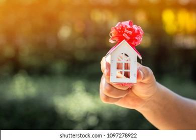 The buying a new real estate as a gift to family or the one loved concept, a woman hand holding a home model tied with red ribbon in the public park.