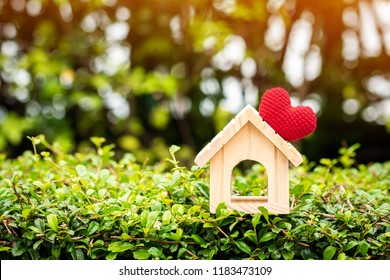 The buying a new real estate as a gift to family or the one loved concept, a home model tied with red heart put on the wood on sunlight in the public park.