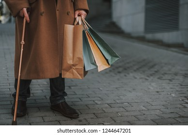 Buying presents. Cropped portrait of stylish gentleman in coat holding shopping bags and walking stick