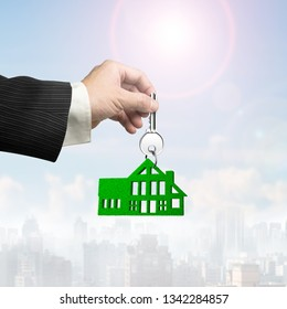Buying or renting green energy house concept. Man hand holding silver key with green grass house shape keyring, on sunlight sky cityscapes background.
