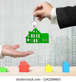 Buying or renting green energy house concept. One man hand giving silver key with green grass house shape keyring to another, on city buildings doodles wooden wall background.