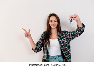 Buying and renting real estate. A smiling woman in a plaid shirt holds a bunch of keys and points with her free right hand to the left. White background and copy space
