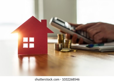 Buying and selling houses and real estate prices concept. Man using calculator to count rent, money or home insurance cost. Calculating mortgage, loan or investment.