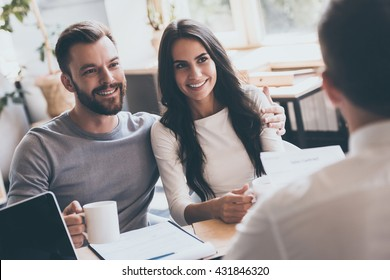 Buying something special. Young loving couple bonding to each other and looking at man sitting in front of them at the desk and holding some document