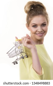 Buying things at market shops concept. Happy smiling woman hand holding small tiny shopping cart trolley