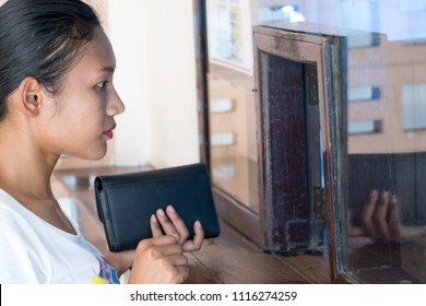 Buying a ticket at counter with window of the box office. Woman buying a train ticket at a railway station.