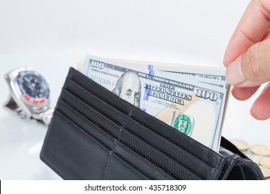 Buying time / hand holding a dollar banknote trying to buy a clock