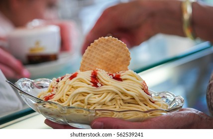 Buying Traditional German Treat: Spaghetti Eis with Red Strawberry Sauce and a Wafer in a Ice-Cream Shop in Hamburg