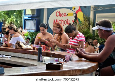 BUZIOS, BRAZIL - February 24, 2013: People sitting in restaurant, using cell phones instead of talking to each other. Compulsive use of the cell phone.