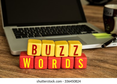 Buzzwords written on a wooden cube in front of a laptop