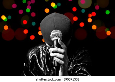 bw asian vocalist holding dynamic microphone with colourful bokeh in concert for music or singing contest background