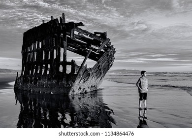 B&W of boy stands by the Peter Iredale shipwreck in the early evening light in northwest Oregon.