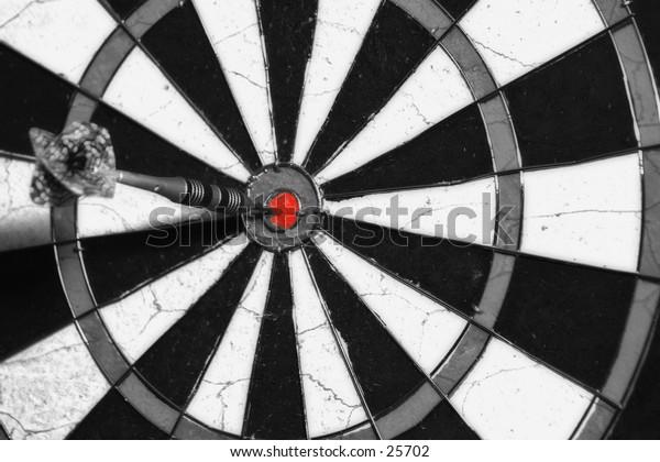 B/W dart board with a red bullseye.
