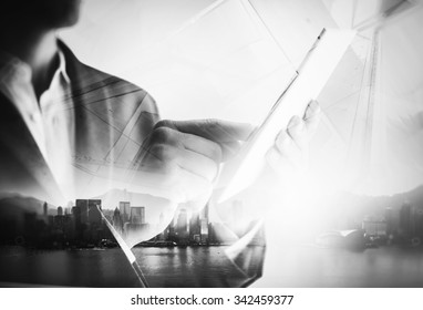 BW double exposure of city and business man using digital tablet.