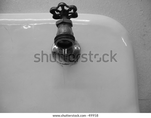 ( B&W ) A Drip of Water from a Laundry Sink Faucet