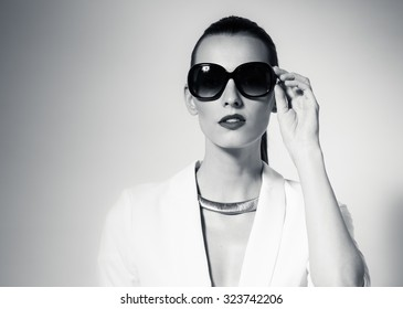B&W fashion portrait of female wearing sunglasses.