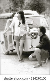 B&W /Gorgeous bride and groom having fun with red retro car in nature
