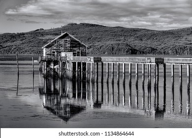B&W of historic pier and shop on Tillamook Bay in Garibaldi, Oregon.