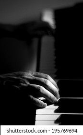 B&W image of hands on piano keys, selective focus