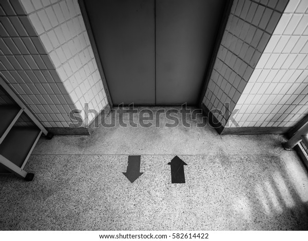 B&W Interior corridor view facing the entrance of elevator or lift doors with navigation arrow symbol on the floor.