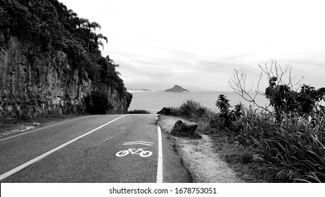 BW landscape of road shared with bike path, where mountain meets the sea