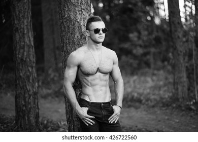 BW outdoor portrait of muscular young man in sunglasses.