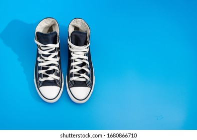 B/w pair of trendy fashion sneakers lying on blue background. Space for text