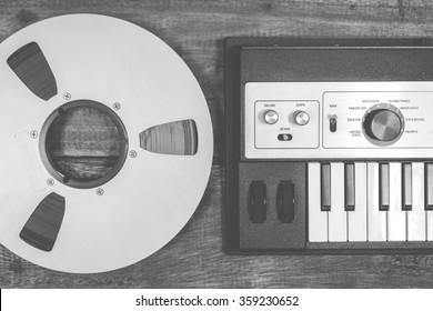 BW photo of analog studio reel tape & digital music synthesizer keyboard