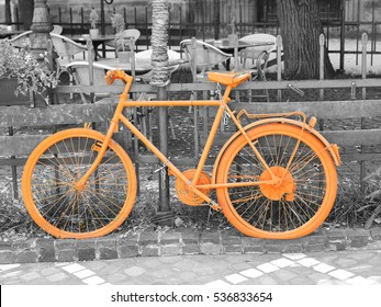 b&w photo of old orange bike on the fence of the coffee shop