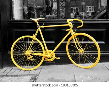 b&w photo of old yellow bike on the window of the coffee shop