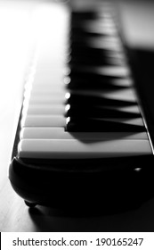B&W shot of a small piano keyboard, dramatic lighting and contrast, selective focus