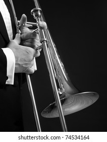 B&W slide trombone held next to a tuxedo clad torso, isolated on black.