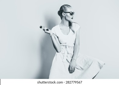 bw woman in skirt and sunglasses with lollipop in studio