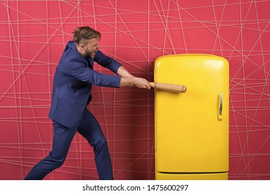 By force or persuasion. sexy man in stylish jacket. confident businessman in suit. Businessman with bat hit yellow fridge. angry man. Feel the success. Business fashion. Male formal fashion.