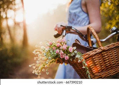 Bycicle girl with floral basket on sunset