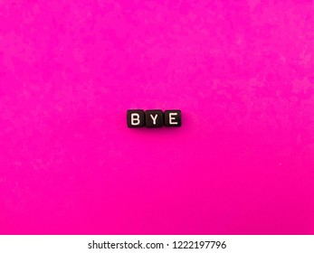 Bye. Farewell. Black alphabet letters on hot pink background. Vivid color. Colorful minimalism. Pop of color.