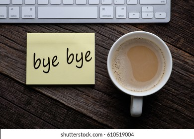 Bye bye. Message on sticky note on wooden table with coffee and keyboard.