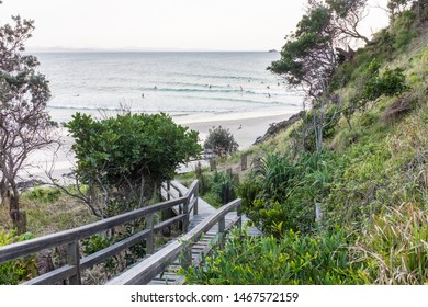 BYRON BAY, AUSTRALIA - SEPTEMBER 20, 2014: Surfers riding a wave or waiting to catch a wave at Wategos Beach, Byron Bay, NSW, Australia