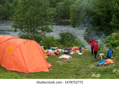Bystraya river, Kamchatka / Russia - July 30 2019: Campsite on the river bank. People around campfire. Big orange tent. Hiking and boat trip goods spread on the ground. Packing of the encampment.