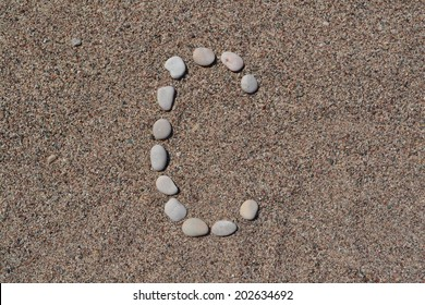 C letter made of stones on sand
