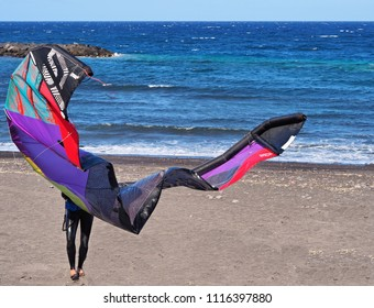 A c on the beach with kitesailing in the wind. You can only see the surfer's legs and the sail flying far and colorful. Behind the Atlantic